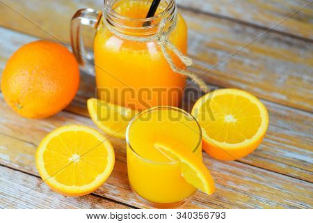 Orange Juice In The Glass Jar And Fresh Orange Fruit Slice On Wooden Table / Still Life Glass Juice