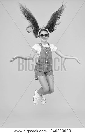 Amazing Long Hair. Cute Small Girl With Long Hair Jumping On Yellow Background. Adorable Little Chil