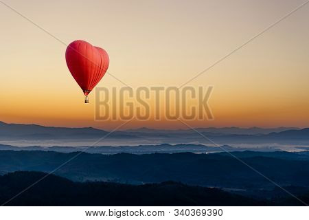 Red Hot Air Balloon In The Shape Of A Heart Flying Over The Mountain