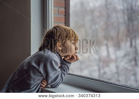 Happy Adorable Kid Boy Sitting Near Window And Looking Outside On Snow On Christmas Day Or Morning.