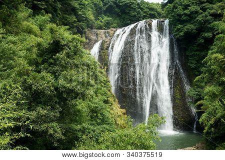 Waterfall Falling Along The Bedrock In Back Of Green Forest