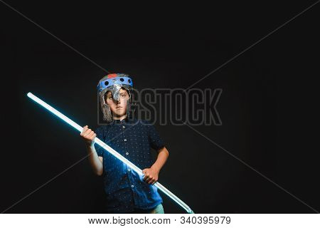 A Kid With A Light Saber In His Hands Play In A Superhero Battle.
