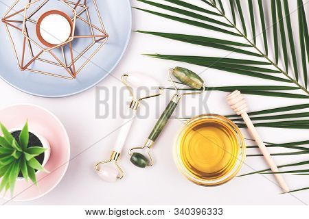 Beauty Composition With Trendy Pink And Green Jade Rollers, Honey And Candle On Grey Background. Sel