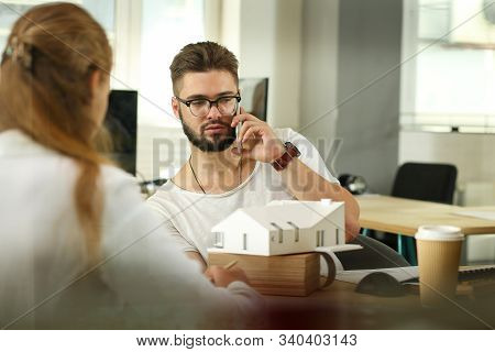 Portrait Of Handsome Smart Businessman In Glasses With Cellphone. Male In Casual Clothes At Biz Meet