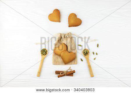 Heart Shaped Cookies On Cotton Bag On White Wooden Background With Cinnamon And Spoons With Cardamon