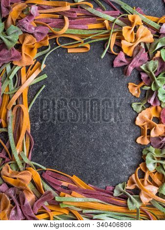 Frame Of Raw Pasta, Farfalle Bow-tie, Fettuccine Or Tagliatelle Colorful Pasta On Grey Background Wi