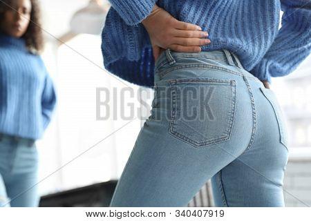 Woman Wearing Jeans Near Mirror Indoors, Closeup