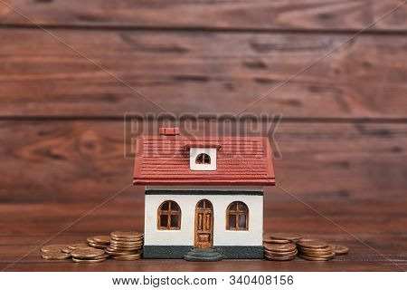 House Model And Coins On Wooden Background