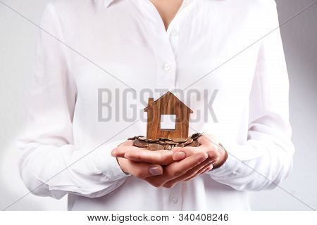 Woman Holding House Model And Coins, Closeup