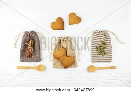 Heart Shaped Cookies, Cinnamon And Spoons With Cardamon On Cotton Bags On White Wooden Background. F