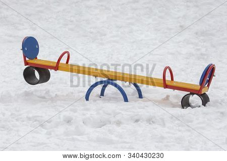 Empty Playground In Winter, Swing Tree Metal Multicolored Funny Flip Flap. Lots Of White Snow With T