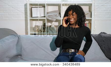 Attractive African Girl With Fleecy Hair In Black Pullover Talks On Modern Smartphone Sitting On Gre