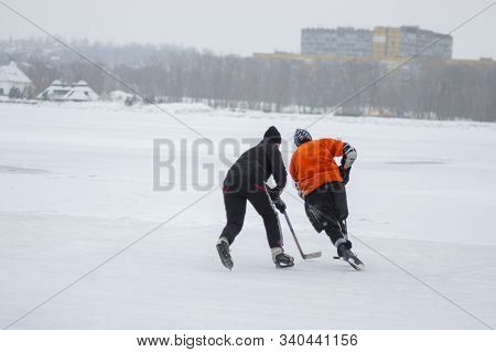 Dnipro, Ukraine - January 28, 2018: Teenager Fighting With Dad For The Pack While Playing Hockey On
