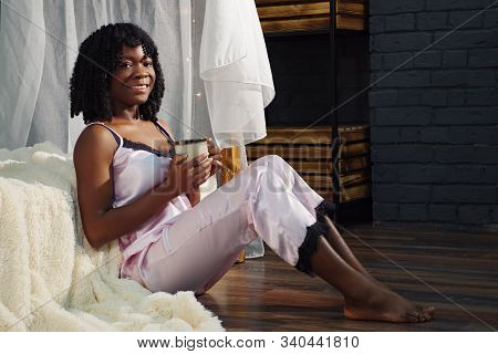 Pretty Black Lady With Fleecy Hair Sits On Floor Leaning On Bed And Drinks Coffee From White Cup In