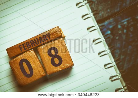 February 8th. Day 8 Of Month, Handmade Wood Cube With Date Month And Day Placed On A Lined Notebook