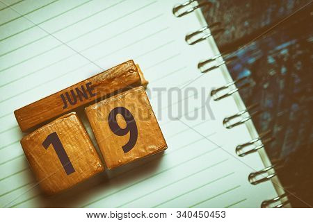 June 19th. Day 19 Of Month, Handmade Wood Cube With Date Month And Day Placed On A Lined Notebook On