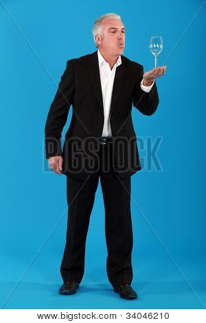 Businessman blowing on a wine glass