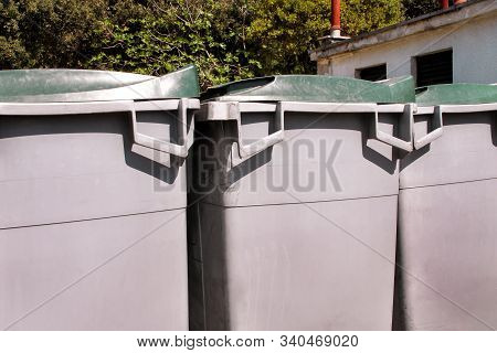 Large Garbage Containers, Trash Dumpsters And Bins Standing In Row. Orderly Stowed Garbage Cans Read