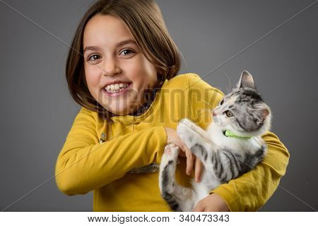 Portrait Of Happy Young Little Girl With Calico Kitten Cat.