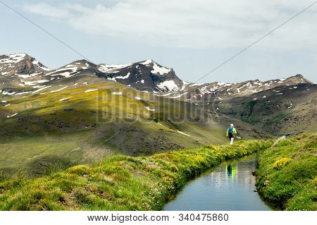 A Man Hiking In The High Mountains