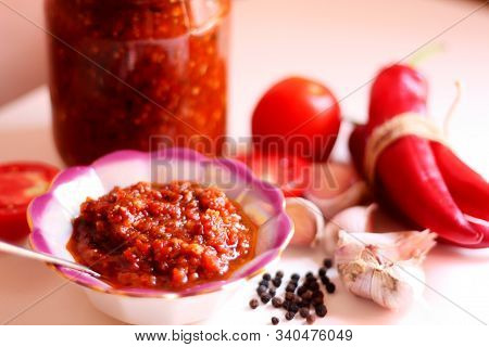 Hot Chilli Pepper Tomato Sauce Paste With Garlic In Bowl Closeup. Adjika, Hot Harissa Sauce - Spicy