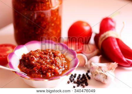 Hot Chilli Pepper Tomato Sauce Paste With Garlic In Bowl Closeup. Adjika, Hot Harissa Sauce - Spicy