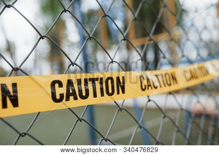 Yellow Caution Tape On The Metal Fence At Daytime. Crime Scene.