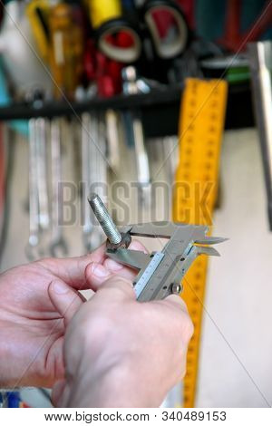 Worker With Tools In Hands. Mechanic Is Checking And Measuring Screw Size With Stainless Steel Calip