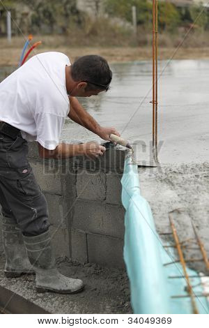 Builder laying foundations