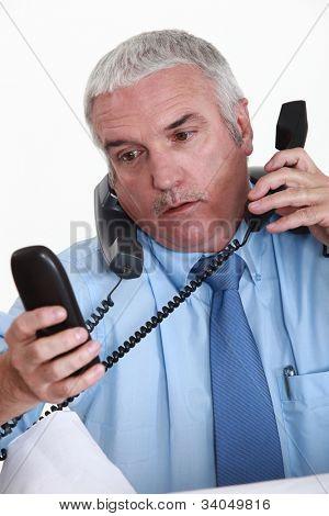 Overwhelmed white collar worker answering telephones