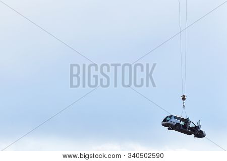 Discarded Old Car Without Wheels, Lifted Up By Cables Against A Sky Before Recycling, With Text Spac