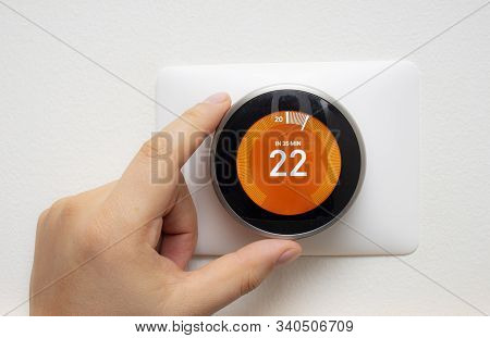 Smart Thermostat With A Person Warming Up The Room Temperature With A Soft Shadow