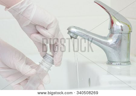 Tap Water Analysis Quality Control Concept. Hand With A Flask And Water Tap Ckose Up.