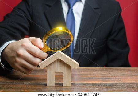 A Man Is Studying A House Through A Magnifying Glass. Fair Value Of Real Estate. Property Valuation.