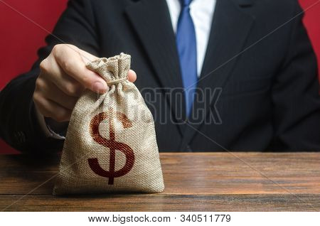 A Man Holds Out A Bag Of Money. Bank Deposit. Donations. Financial Social Assistance. Provision Of M