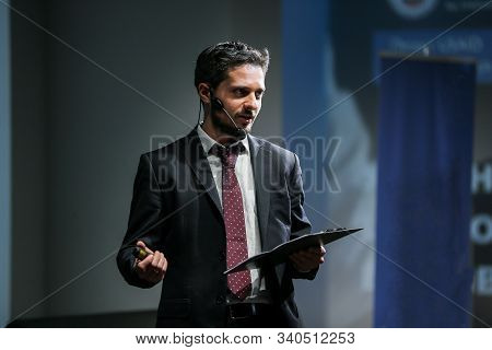 Attractive And Confident Successful Man With Headset Speaking At Corporate Business Coaching And Tra