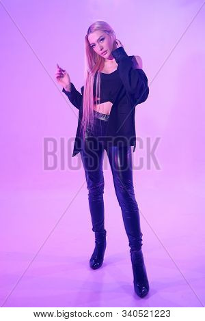 Attractive Blonde Woman Sitting On The Chair Over Pink Background