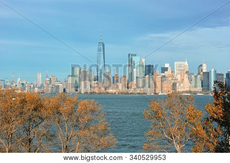 NEW YORK, NY - 04 NOV 2019: The Manhattan Skyline seen from Ellis Island with beautiful fall trees in the foreground.