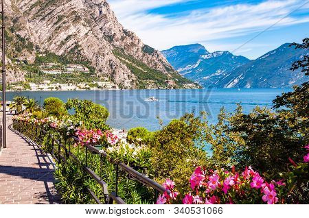 Cozy City Street Of Limone Sul Garda With Paving Stone Sidewalk, Blooming Flowers On A Metal Railing