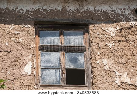 Old Weathered Broken Window On Neglected Adobe Clay Rural House Wall