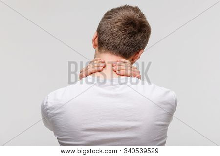 Back View Of Man In White Top Touching Her Pain In His Neck And Back, Feels Pain, Massages The Painf