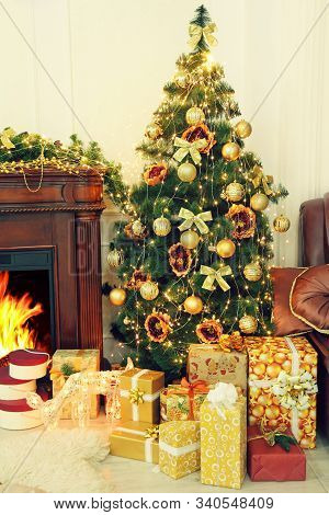 Christmas Fir-tree, Golden Christmas Decorations And Gifts Near Fireplace In Interior. New Year. Chr