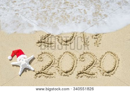 2020 Year Is Coming Concept, Beach Background Near Ocean With Starfish In Santa Hat