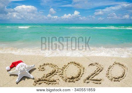 2020 Year Beach Background Near Ocean With Starfish In Santa Hat
