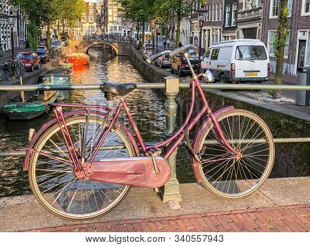 Red Bicycle Leaning On Canal Railing In Amsterdam