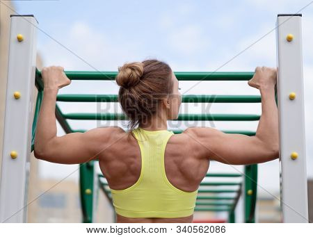 Female Well-muscled Back, Close Up. Caucasian Attrctive Woman In Short Top Doing Chin-up Outdoor, Se