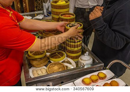 Waitress Catering Dimsum In Bamboo Steamer Boxes In Chinese Restaurant