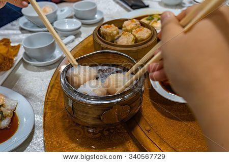 Human Using Chopsticks Eating Dimsum Steamed Shrimp Dumpling