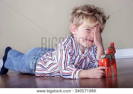 Smiling young boy covering his eye and playing with a swedish wooden horse