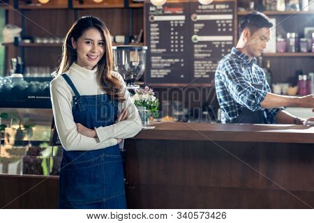 Portrait of young adult asian owner of cafeteria cafe standing in front of barista bar in coffee shop with employee working in background. Using for entrepreneur startup SME concept.